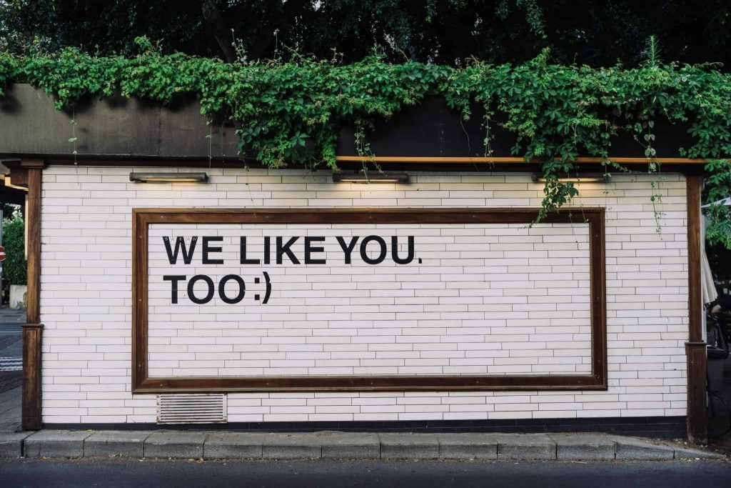 """A photograph of a white brick wall with text overlay """"we like you, too :)"""""""