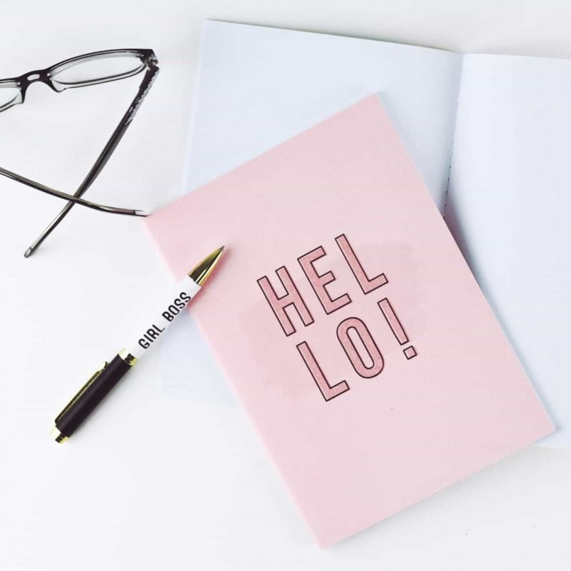 "Flat lay photograph with glasses, a pen that says ""girlboss"", note paper, and a pink book with a cover that says ""Hello!"""