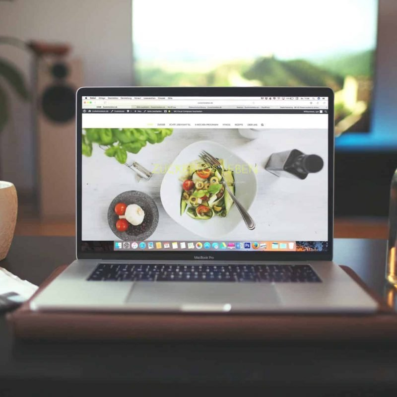 A photograph of a food blog on a laptop. The laptop is sitting on a desk in front of a window.