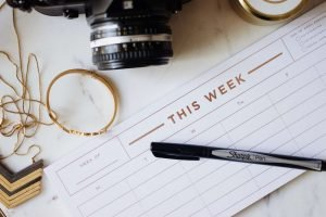"A flat lay photograph of a camera, bracelet, necklace, pen and piece of note paper that says ""This Week"""