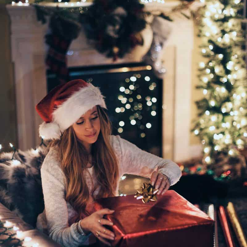 A woman opening a gift at Christmas