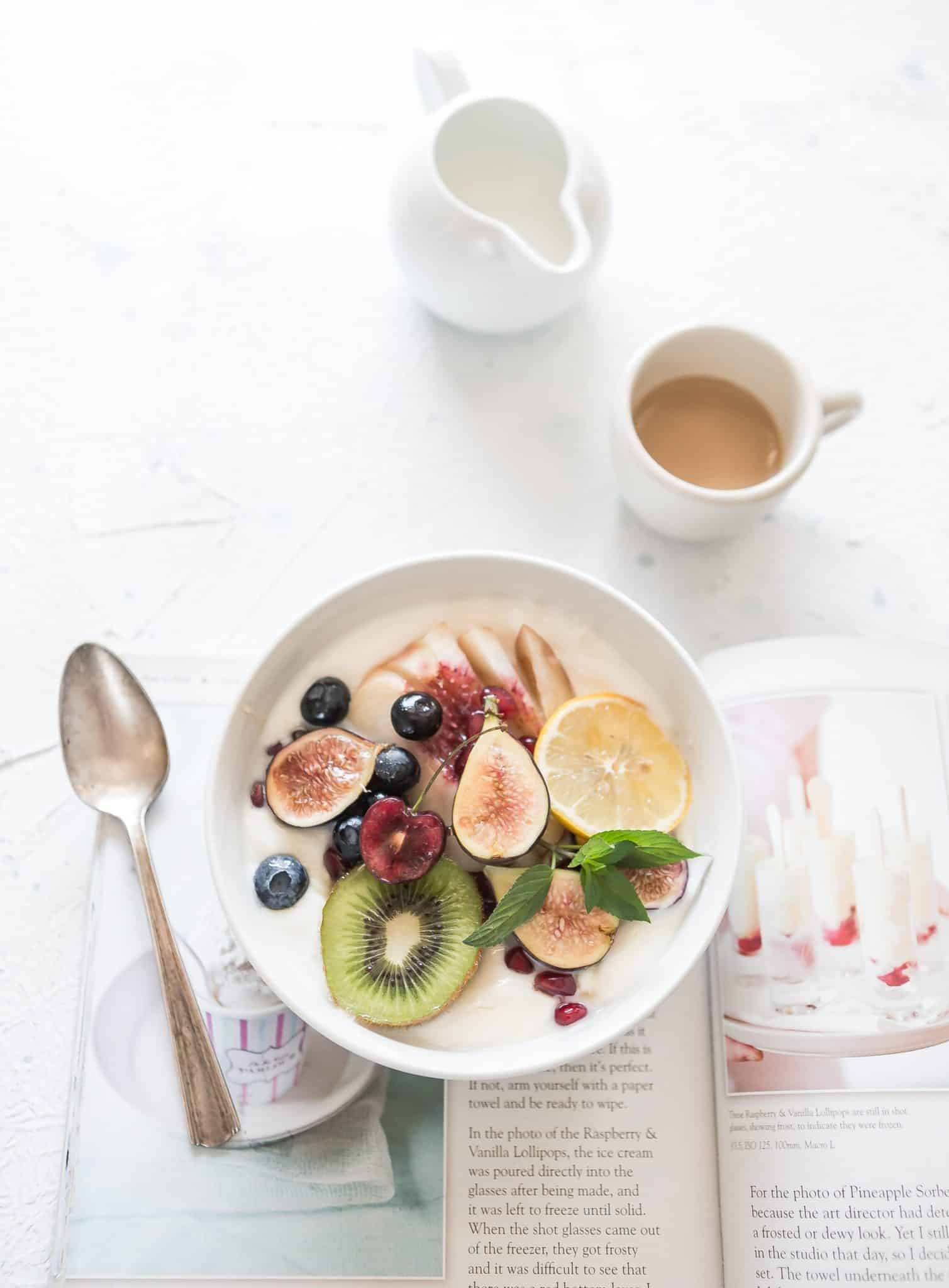 A flatlay photograph of a bowl of fruit in cream sitting on a cookbook, coffee and creamer on table