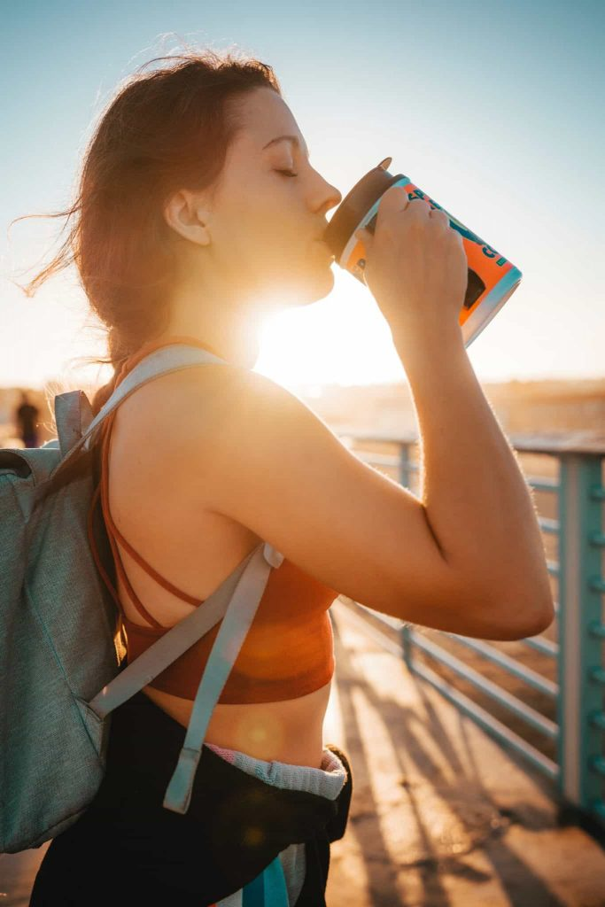 A photograph of a women in a crop top standing int he sun drinking from a cup