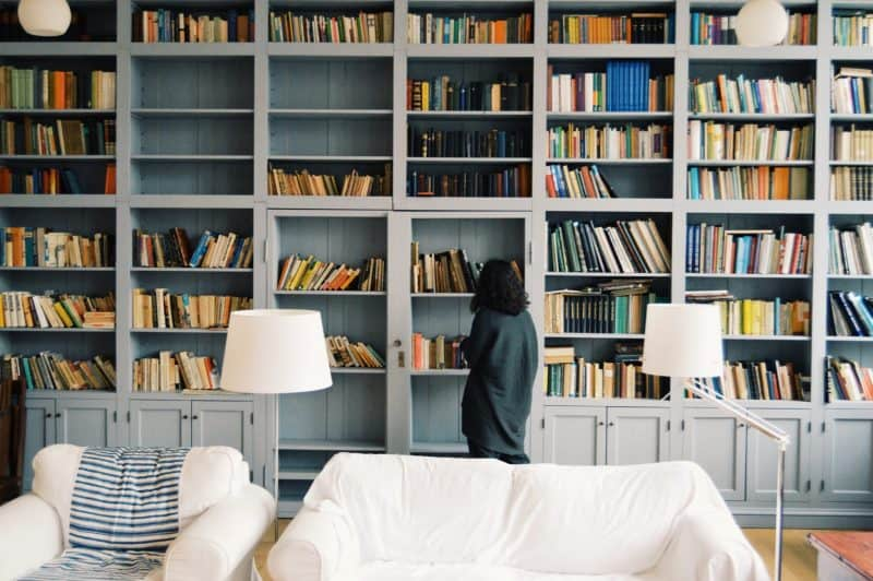 A woman in a library room look at large shelves of books. Symbolic of what im reading.