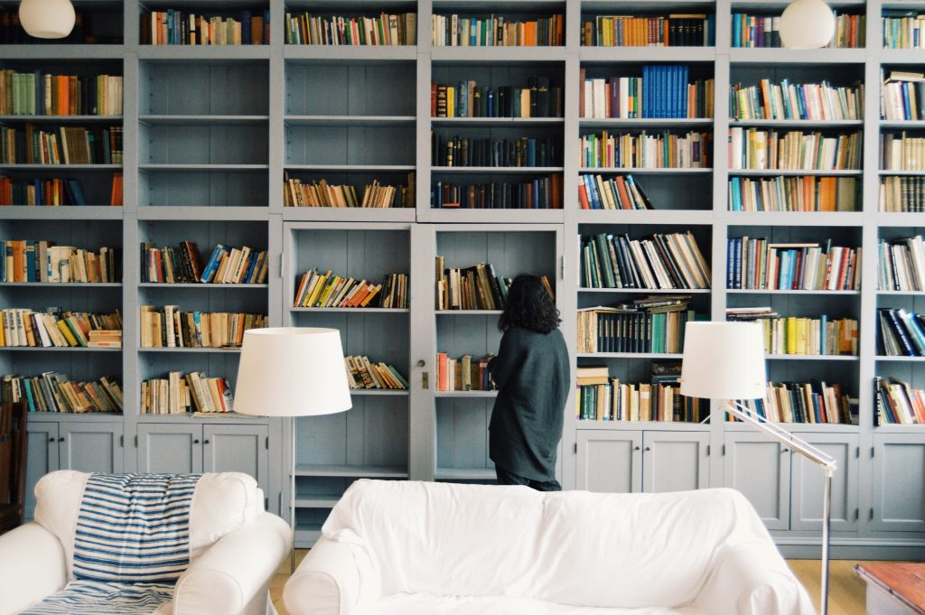 A woman walking in front of a large library bookshelf filled with books