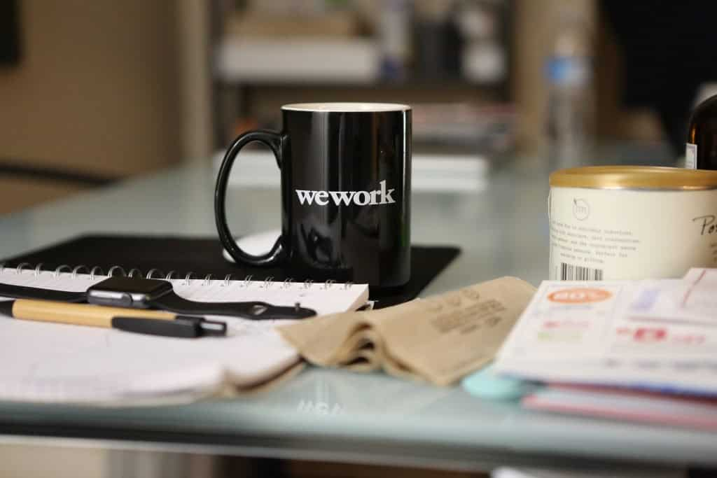 "A mug on a desk with the saying ""we work"" on it"