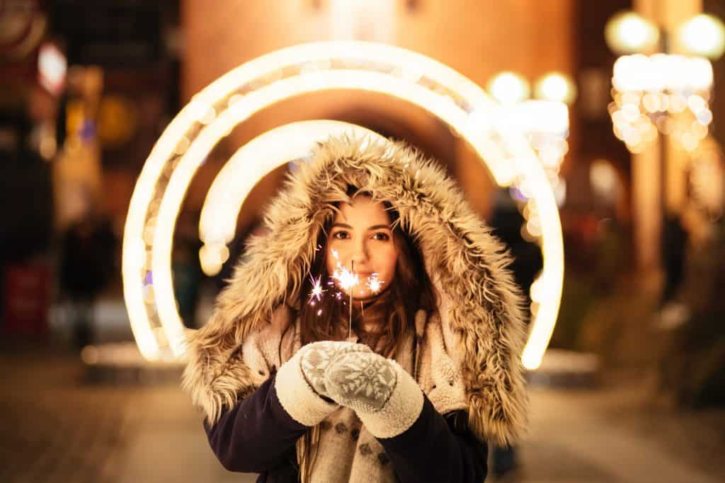 A woman in winter outerwear holding a sparkler at night
