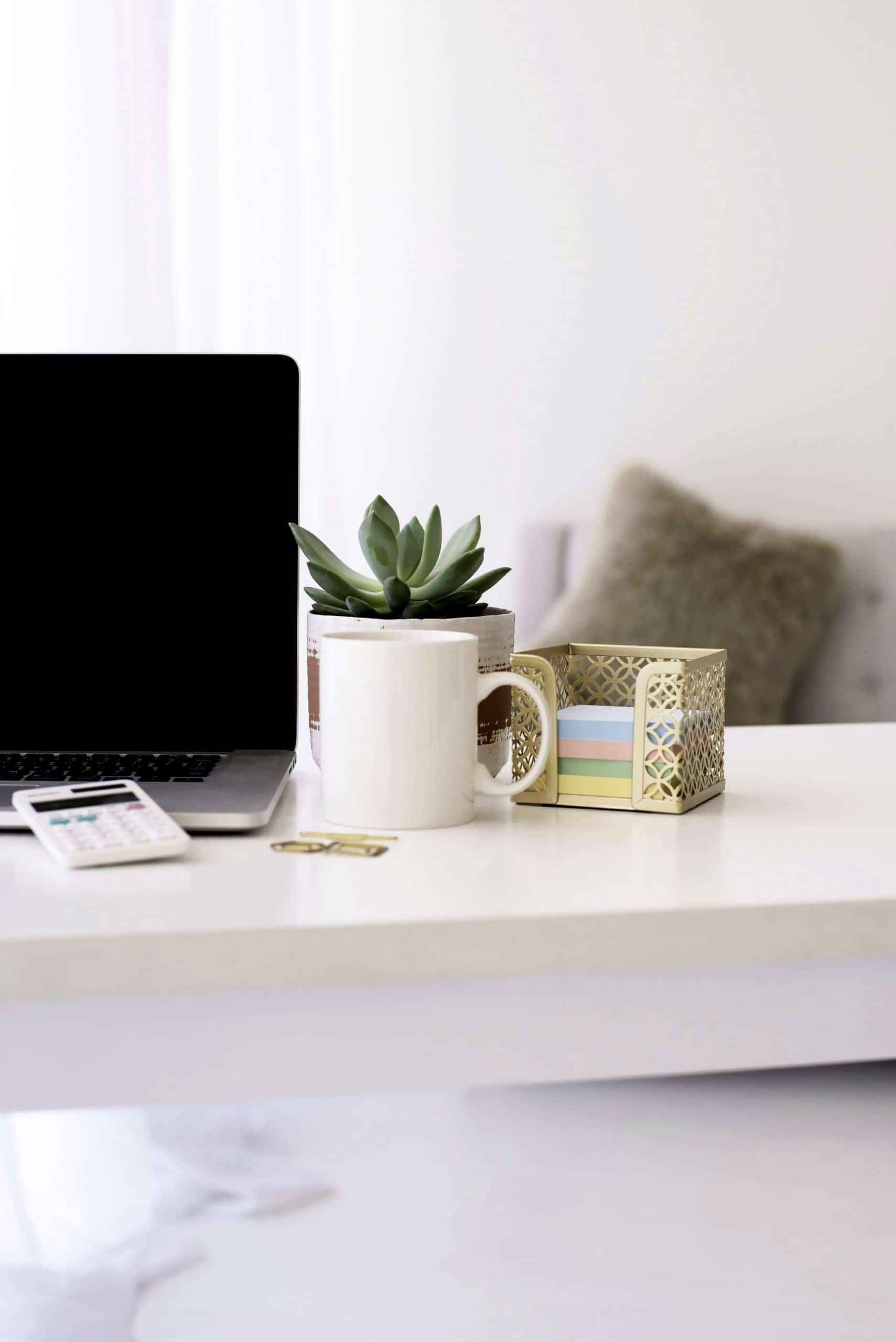 A desk with a laptop and decor