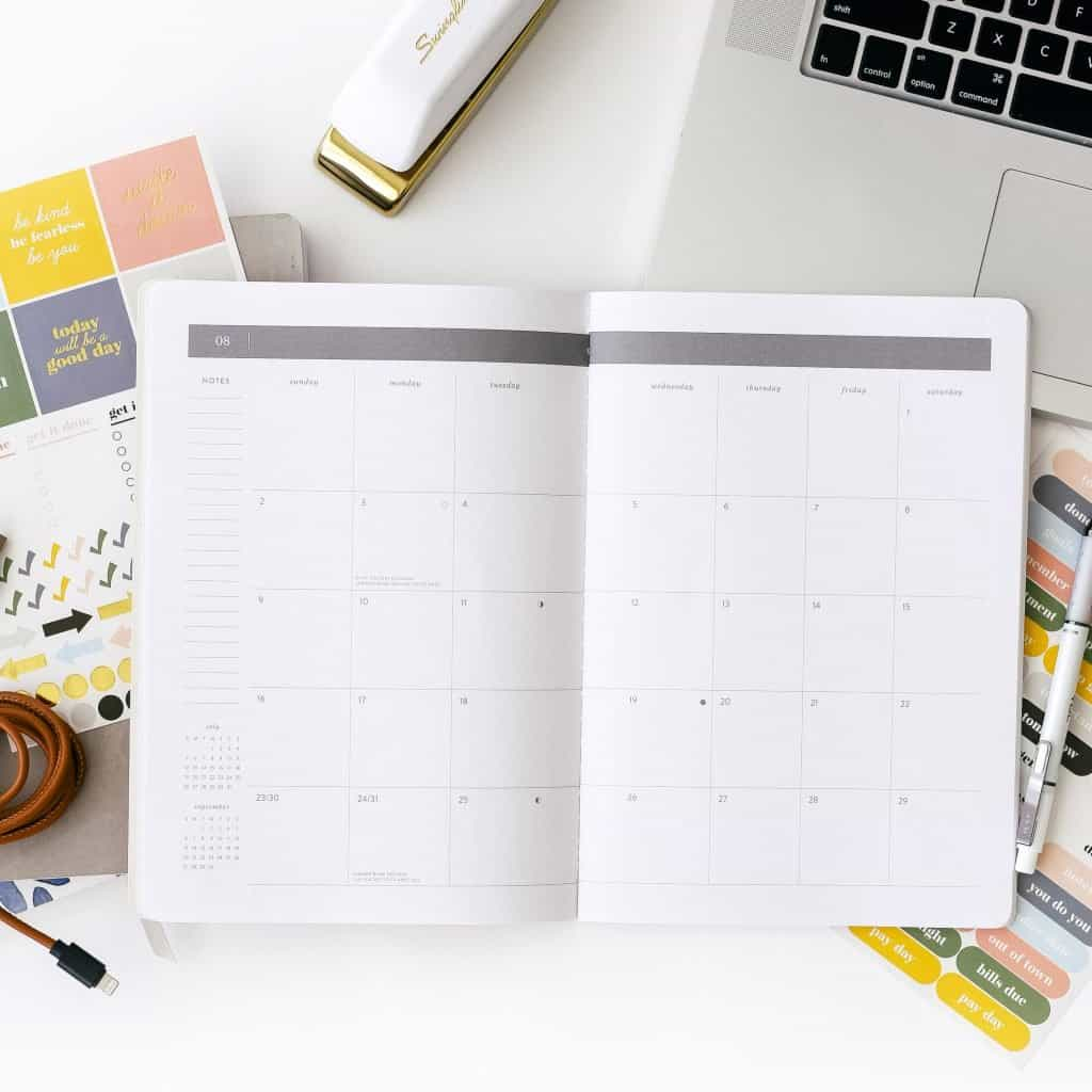 A photograph of a calendar booklet on a desk with other items